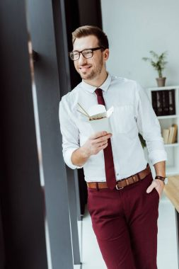 stylish businessman holding box with noodles for lunch in office