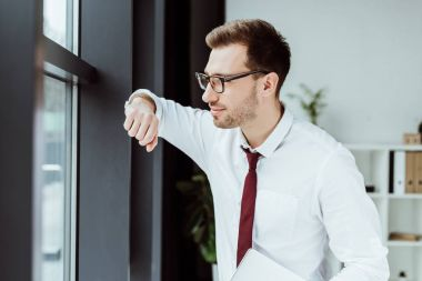 handsome stylish businessman with laptop looking at window in modern office