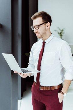 stylish businessman using laptop in modern office