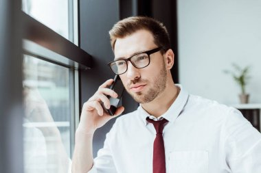 handsome stylish businessman talking on smartphone in office