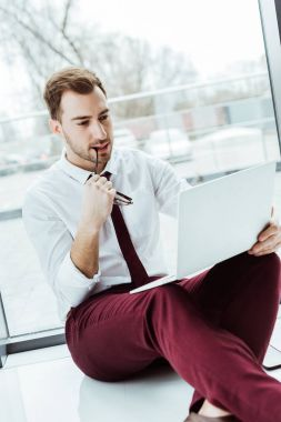 handsome pensive businessman using laptop and sitting on floor