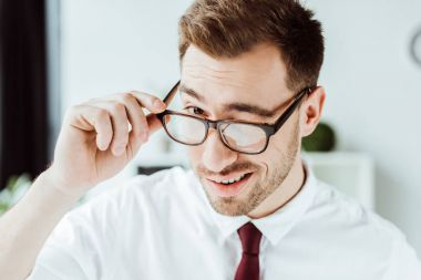 handsome smiling businessman winking in glasses