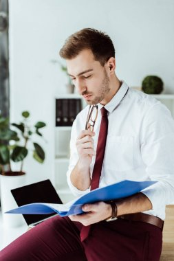 pensive businessman reading documents from folder