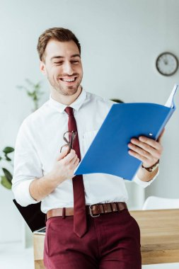 handsome smiling businessman looking at folder with documents