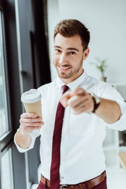 smiling businessman with disposable cup of coffee pointing at you