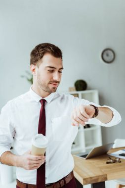 businessman with disposable cup of coffee looking at wristwatch