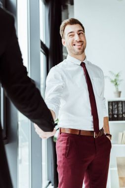 businessman winking and shaking hands with colleague in office