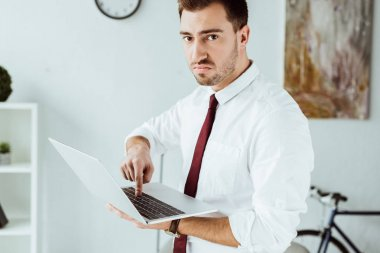 angry businessman in tie using laptop in office
