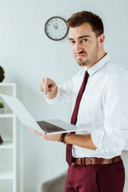angry businessman pointing at laptop in modern office