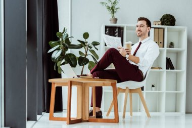 stylish businessman with coffee reading newspaper in modern office with laptop