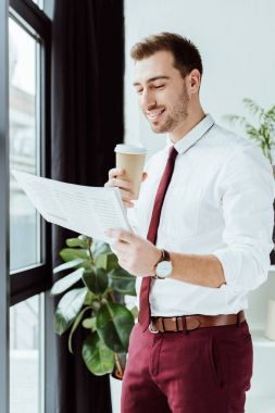 handsome businessman with coffee reading newspaper in modern office