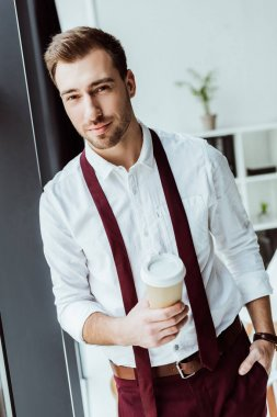handsome businessman with disposable cup of coffee in office