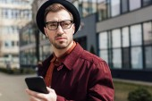 hezký vážný muž v brýle a čepice pomocí smartphonu