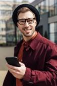 Fotografie pohledný muž v módní brýle pomocí smartphonu