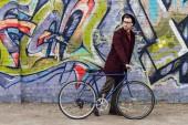 stylové elegantní muž, který stojí s kolo na zeď s graffiti