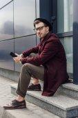 Fotografie pohledný moderní muž pomocí smartphone na ulici