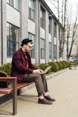 young man working with laptop while sitting on bench