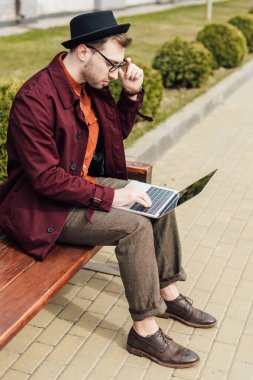handsome young man using laptop while sitting on bench