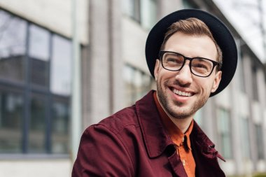 handsome cheerful man in eyeglasses and hat