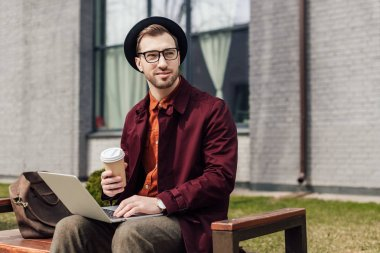 Handsome stylish man with coffee to go using laptop stock vector