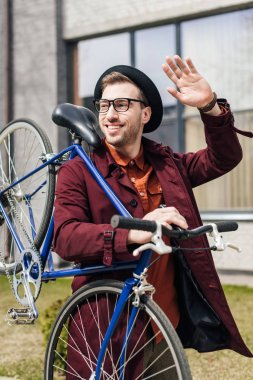 handsome smiling man waving and carrying bicycle