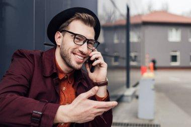 cheerful stylish man talking on smartphone