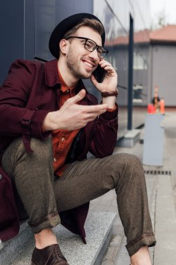 smiling man in eyeglasses and hat talking on smartphone