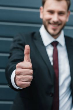 Close-up view of young businessman showing thumb up and smiling at camera stock vector