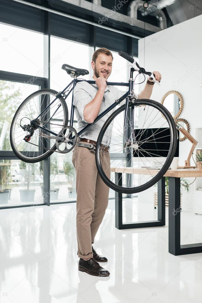 businessman carrying bicycle