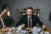 Fotografie angry businessman yelling while sitting at workplace