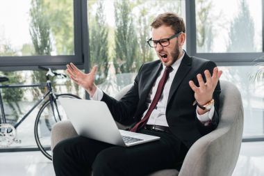 angry businessman yelling while working on laptop