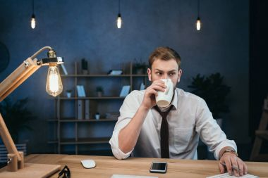 businessman drinking coffee while working at office