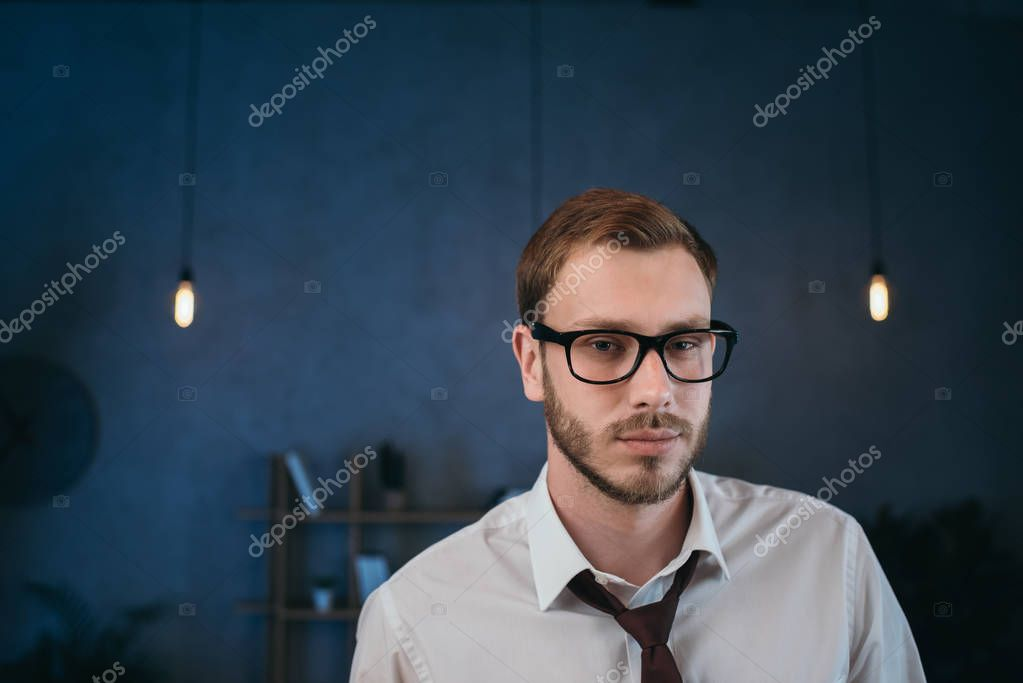 businessman in glasses looking at camera at office