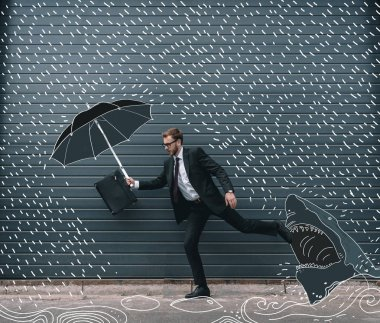 Businessman running with umbrella