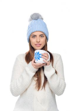 beautiful woman in knitted hat and winter sweater holding cup of hot coffee, isolated on white