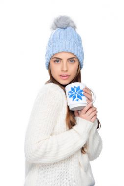 beautiful woman in knitted hat and winter sweater holding cup of coffee, isolated on white