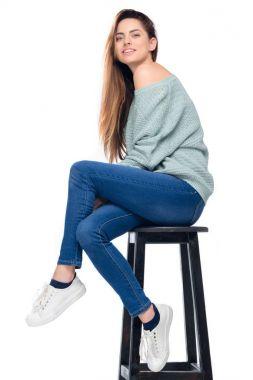 beautiful smiling girl sitting on stool, isolated on white
