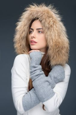 beautiful woman in fur hat and winter outfit, isolated on grey