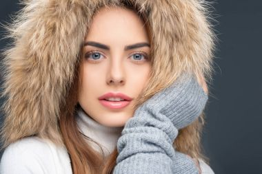 portrait of beautiful woman in fur hat and winter outfit, isolated on grey
