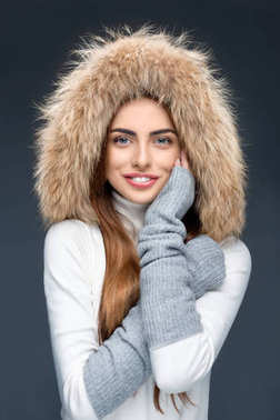 Beautiful smiling woman in fur hat and winter outfit, isolated on grey stock vector