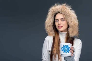 beautiful woman in fur hat and winter outfit holding cup of coffee, isolated on grey