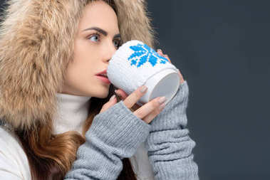 beautiful woman in fur hat drinking hot beverage, isolated on grey