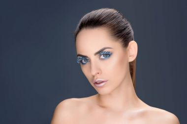 portrait of beautiful woman with winter makeup with glitter, isolated on grey