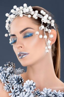 tender woman with hair accessory, christmas pine cones, winter makeup and glitter, isolated on grey