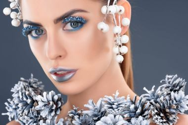 portrait of attractive model with hair accessory, christmas pine cones, winter makeup and glitter, isolated on grey