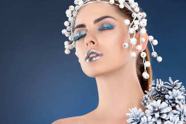 portrait of beautiful model with hair accessory, christmas pine cones, winter makeup and glitter posing for fashion shoot, isolated on blue