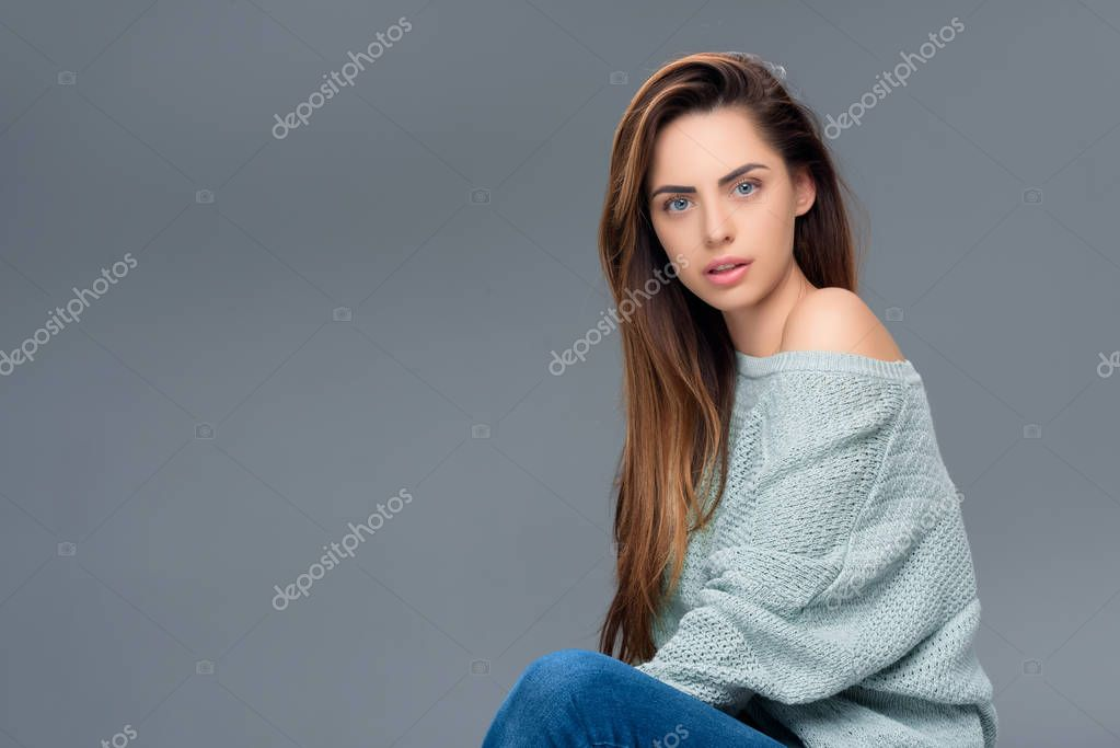 attractive stylish girl in sweater looking at camera, isolated on grey