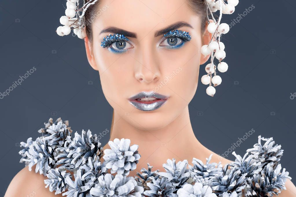 portrait of beautiful girl with hair accessory, christmas pine cones, winter makeup and glitter, isolated on grey