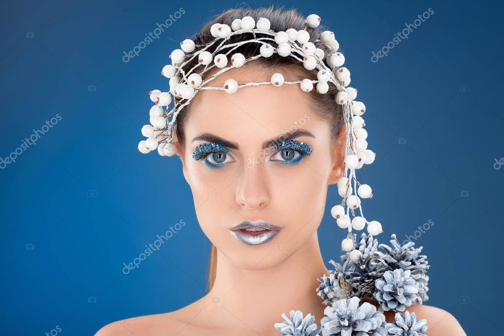 beautiful model with hair accessory, christmas pine cones, winter makeup and glitter, isolated on blue