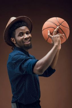 smiling african american sportsman holding basketball ball isolated on brown
